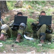 The image shows two soldiers performing a computer test,
