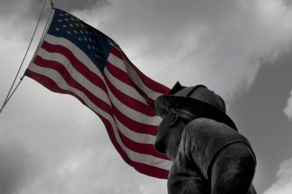 The image shows a statue dedicated to fire fighters who lost their lives during September 11th. The statue points to an american flag.