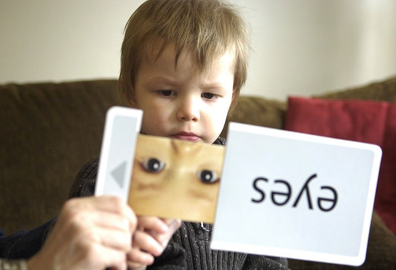 The image shows a child with ASD identifying words from a flash card.