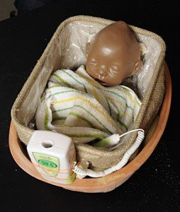 The image shows a baby doll laying in the cooling device developed at Johns Hopkins