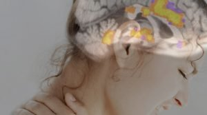 The image shows an fMRI pain brain scan overlayed over a woman's head who appears to be in pain.