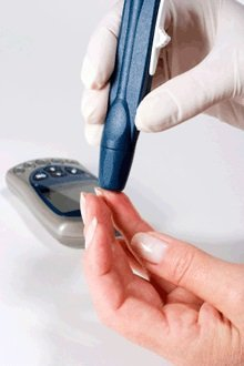 The image shows a patient undergoing a pin prick blood test for diabetes.