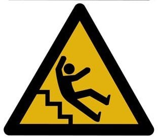 The image shows a caution sign with a person falling down stairs.