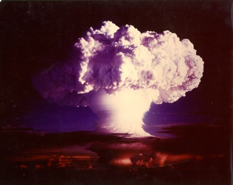 The image shows a mushroom cloud from a nuclear bomb test.
