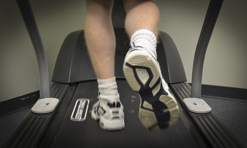 The image shows someone walking on a treadmill.