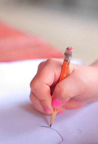 The image shows a child's hand drawing with a pencil.