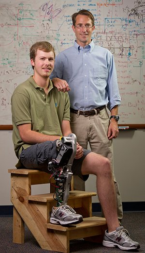 This is an image of a person with the robotic leg and the researcher.