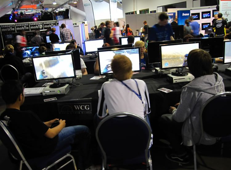 This image shows people playing online games in what appears to be an online gaming conference.