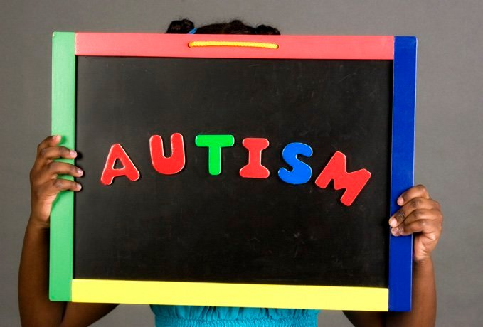 This image shows a child holding up a blackboard with the word Autism written on it.