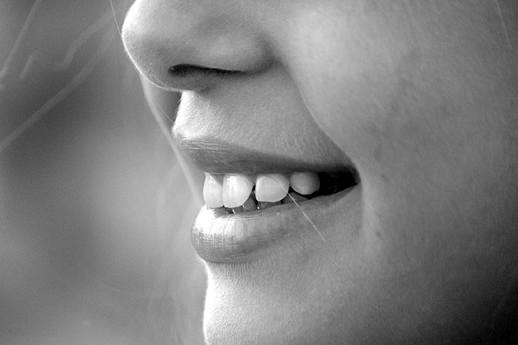 The image shows a girl smiling.