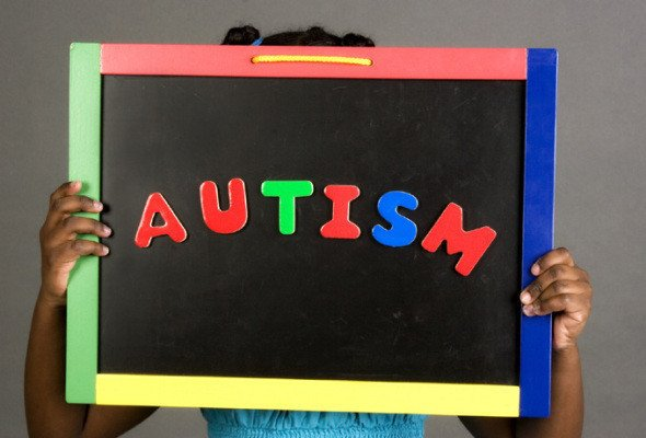 The image shows a child holding a board that reads autism.