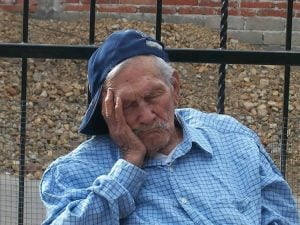 The image shows a old man taking a nap.