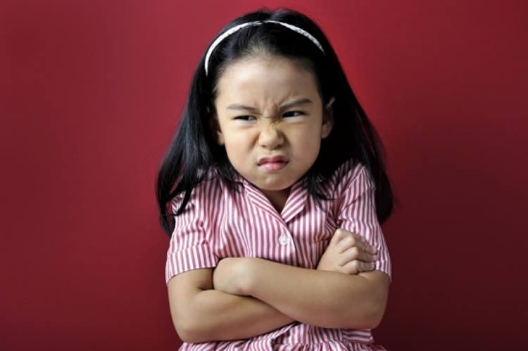 This image shows a young girl pulling an angry face.