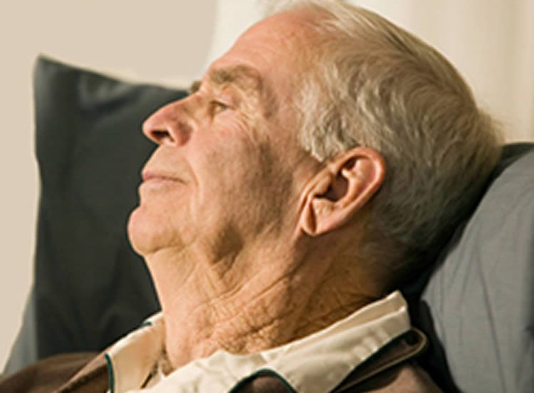 The image shows the an old man sitting in a chair.