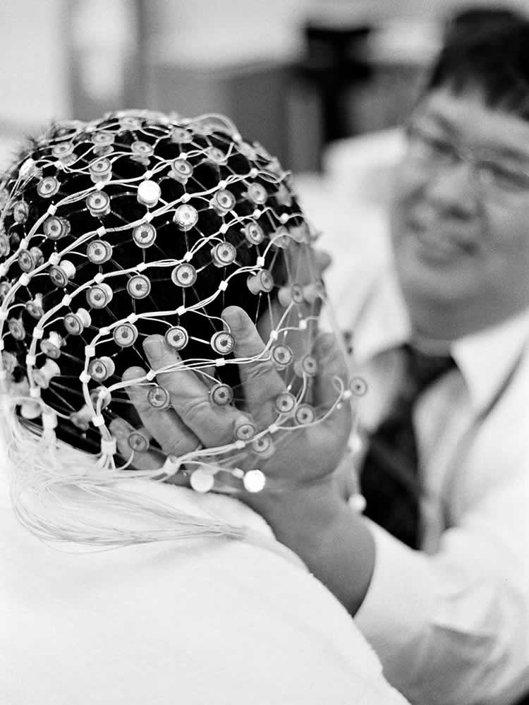 The image shows a person with an eeg cap on. The photo is in black and white.