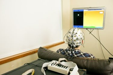 The image shows a test participant hooked up to the EEG machine.