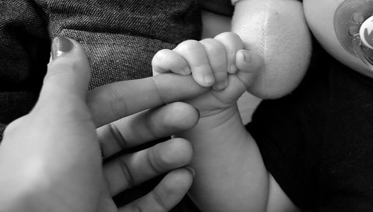 This image shows a mother holding her baby's hand.