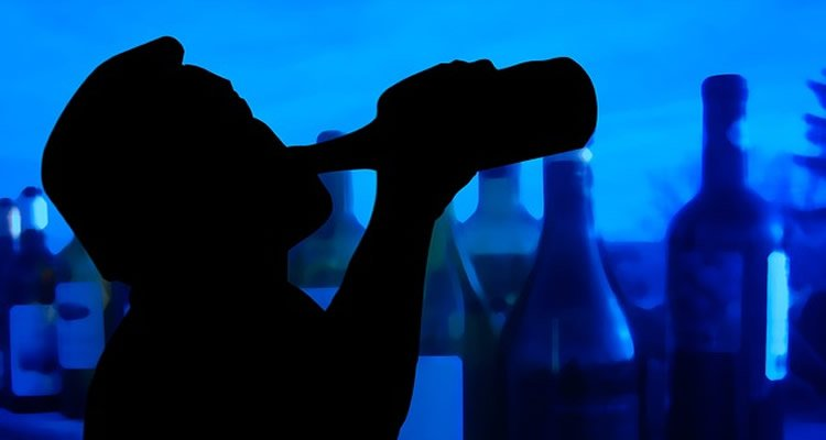 This image shows the outline of a man drinking from a bottle. Behind him is a blue background covered in alcohol bottles.