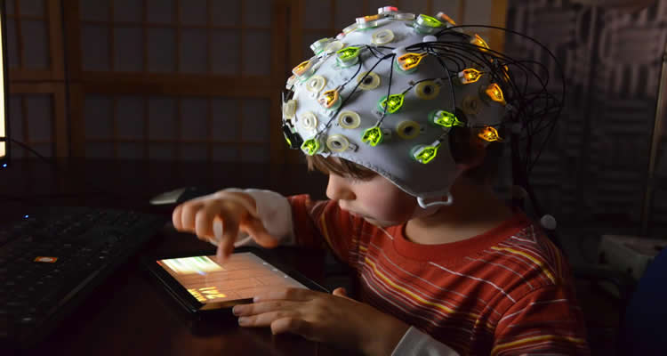 The image shows a child with an EEG cap on their head. The child is playing with a computer tablet.