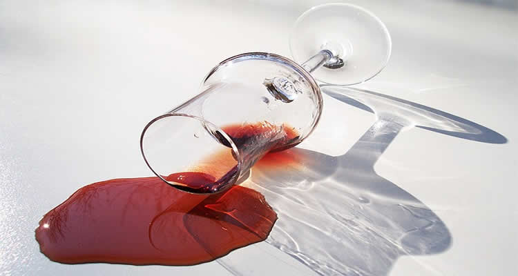 The image shows a spilled wine glass. Red wine is staining a white surface.
