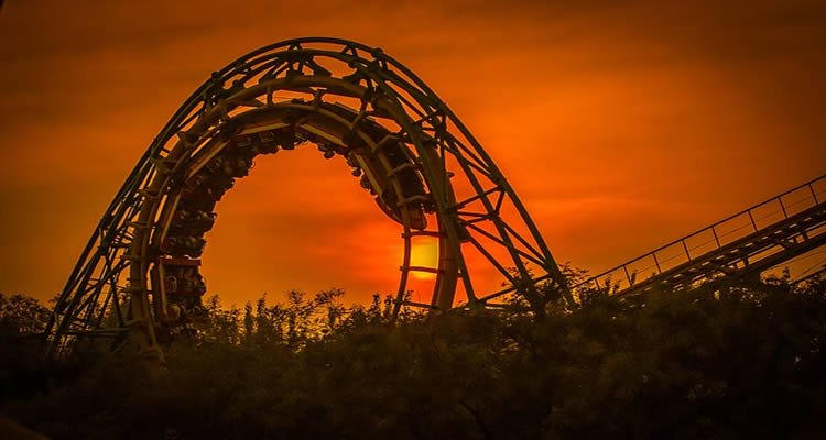 he image shows a roller coaster at sunset.