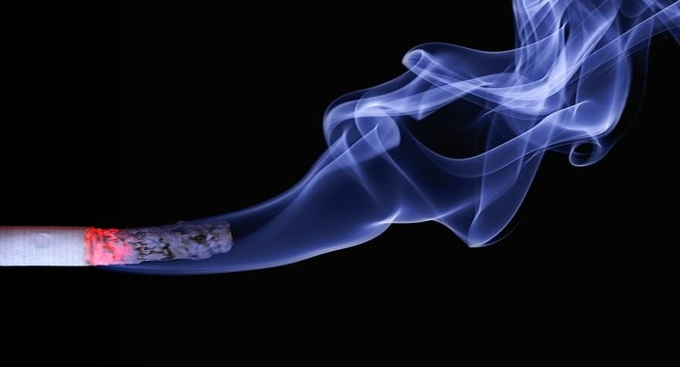 The image shows a burning cigarette and smoke on a black background.