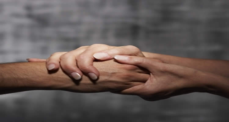 This image shows two people holding hands.