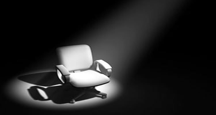 The image shows a white chair under a spotlight.