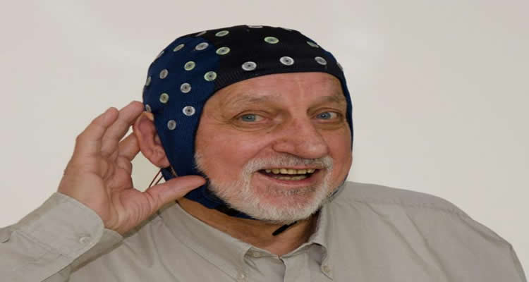 This image shows an older man wearing an EEG cap. His hand is cupping his ear.