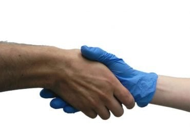 This shows people shaking hands. One has a blue rubber glove on.