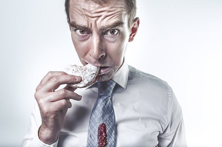 This shows a man looking guilty while eating a cookie.