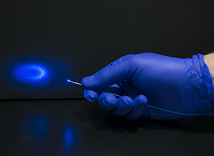 This shows a hand holding a blue laser light.