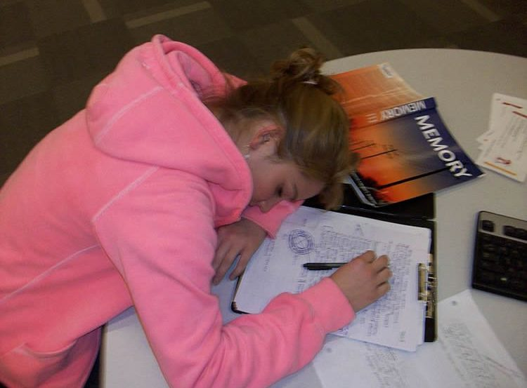 This shows a girl asleep on a desk next to a memory book.