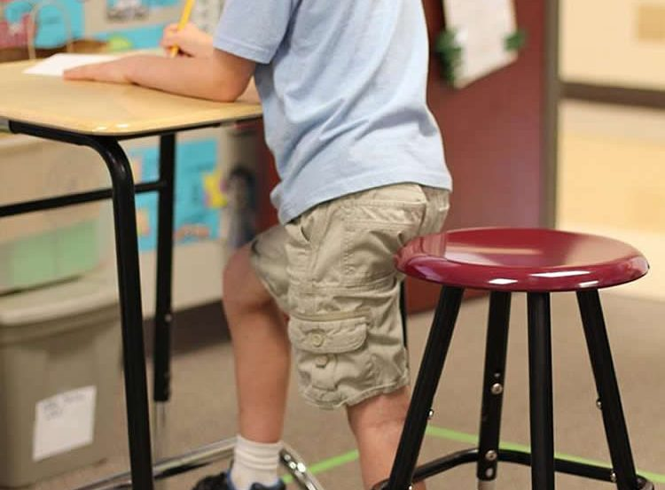 This image shows a little boy standing up at his desk.