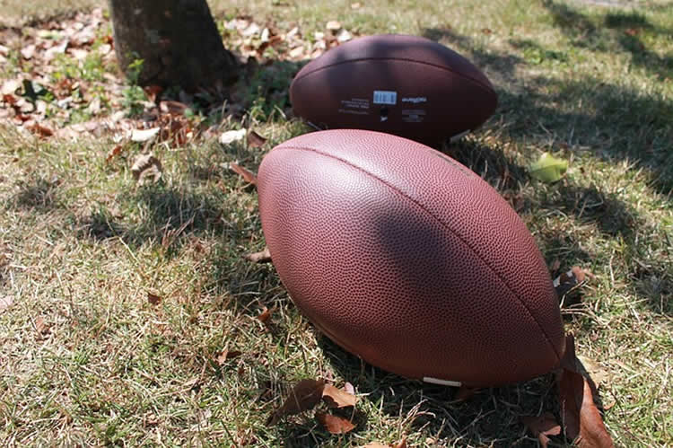 This image shows old footballs laying on a field.
