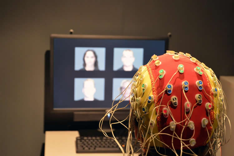 This image shows a person with a EEG cap on, looking at a computer monitor with faces on it.