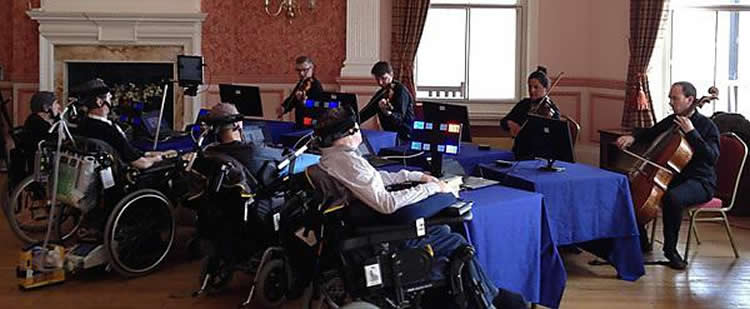 This image shows the people controlling the musicians with EEG helmets on.