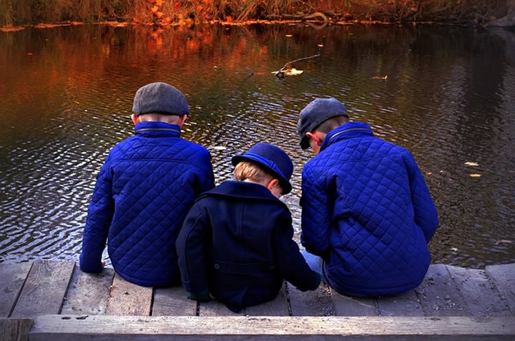 This image shows three brothers sitting by a stream.