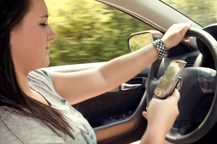 This image shows a woman looking at her cell phone while driving.