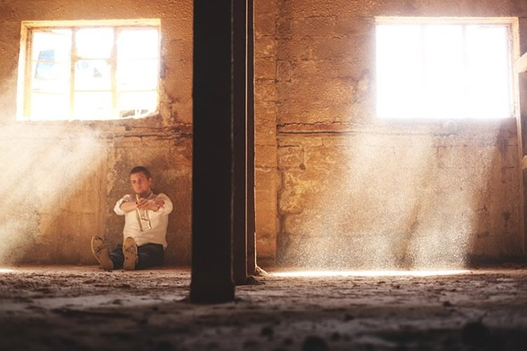 This image shows a man sitting against a wall in a dank looking room.