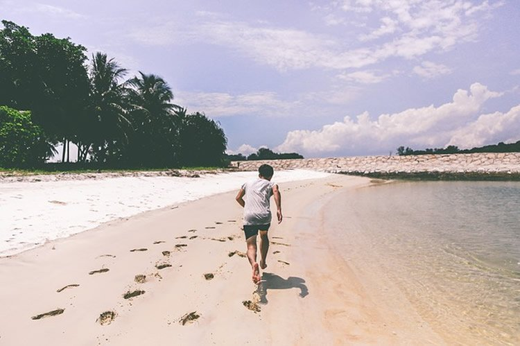 This image shows a man running on a beach.