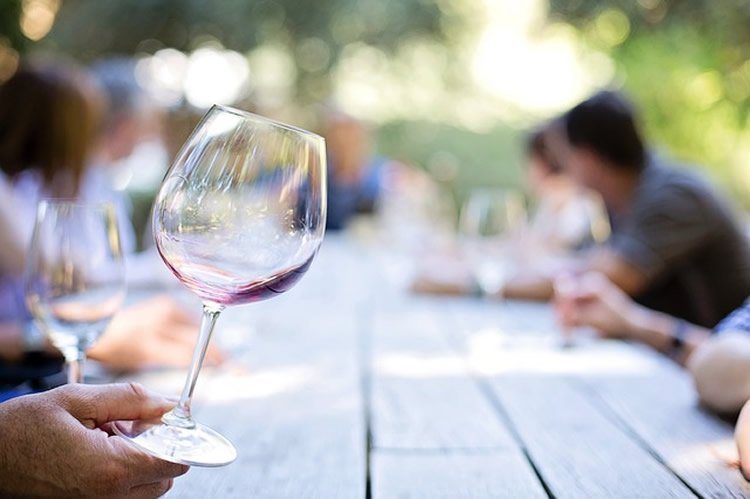 This image shows a hand holding the bottom of a wine glass.