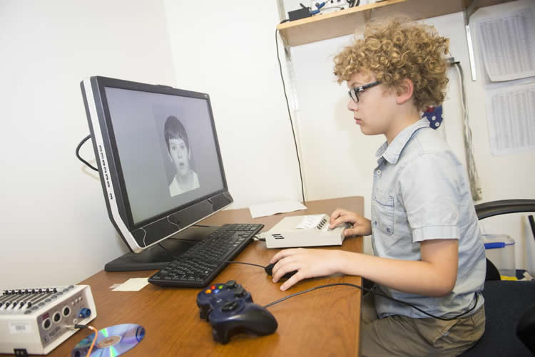 This image shows a child looking at a picture on a computer monitor.