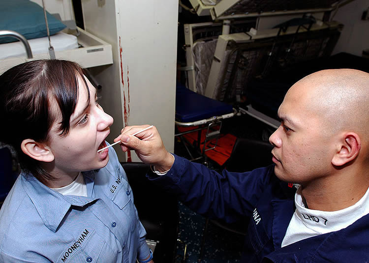 This image is a lady being given a saliva swab test.