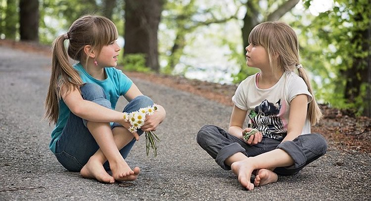 This image shows two little girls sitting on a path.