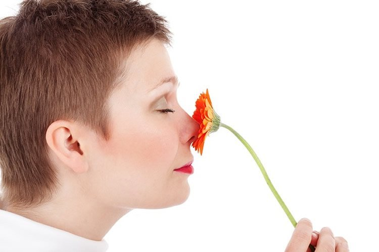 This image shows a woman smelling a flower.