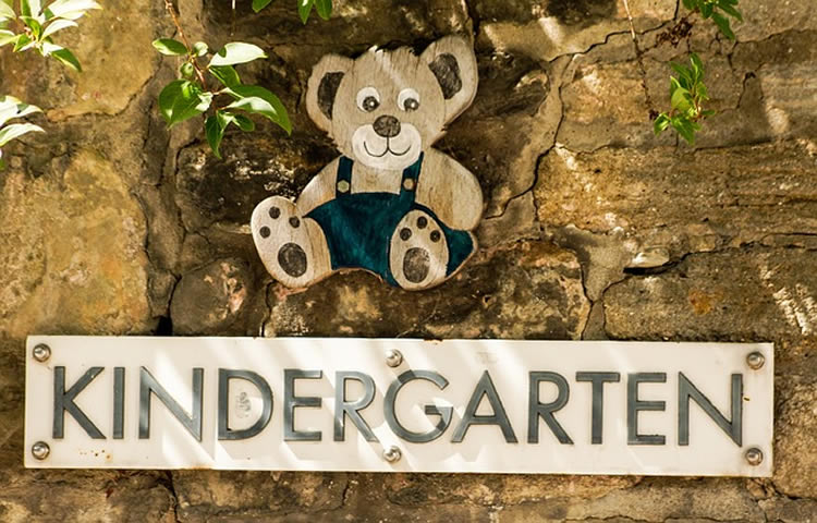 This image shows a sign for a kindergarten with a teddy bear above it.