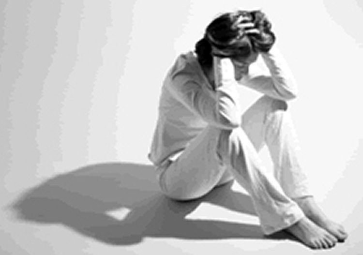 This image shows a woman sitting on the floor and holding her head.