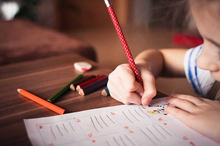Image shows a young child working on a problem in a school book.