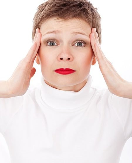Image shows a woman holding her head as if in pain.